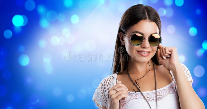 Portrait of young brunette woman hiding her ear by finger, listening music in headphones. Wearing white top, knit. Cardigan and sunglasses.Studio isolate on stock photos