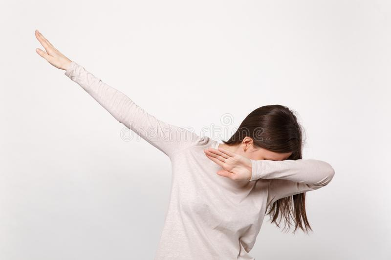 Portrait of young brunette woman in light clothes standing and doing dab dance gesture isolated on white wall background. In studio. People sincere emotions stock photography