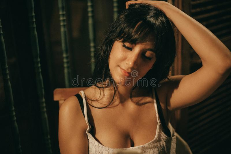 Portrait of a young brunette woman at night with close eyes. Portrait of a young brunette woman at night in a courtyard with close eyes stock photo