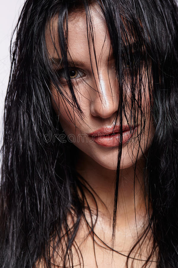 Portrait of a young brunette woman with shining wet make-up and. Shiny moist long hair hairdo royalty free stock photos