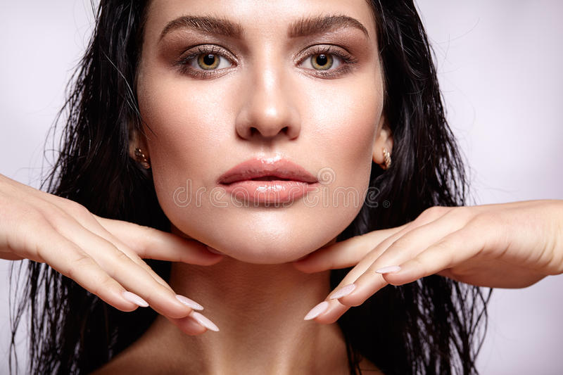 Portrait of a young brunette woman with shining wet make-up and. Shiny moist long hair hairdo stock photography