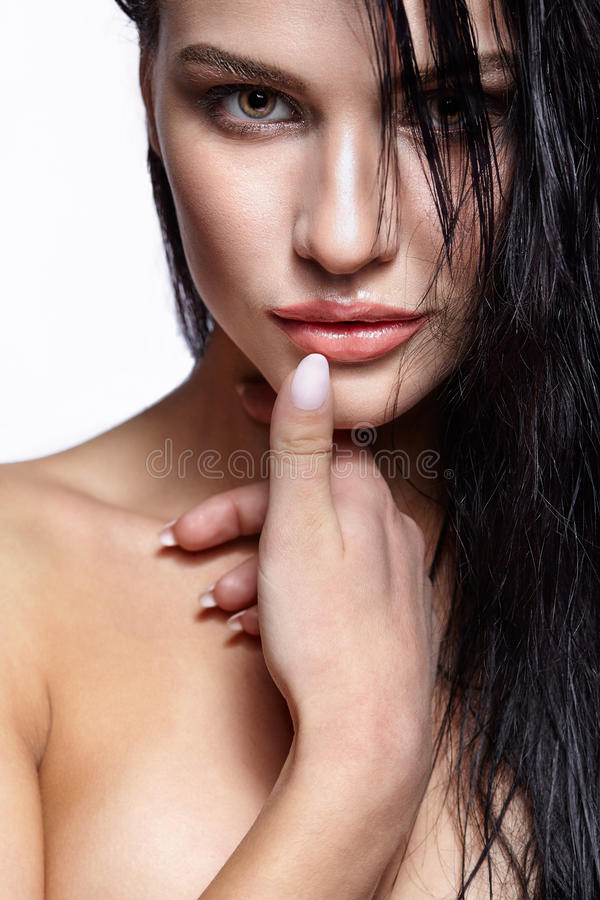 Portrait of a young brunette woman with shining wet make-up and. Shiny moist long hair hairdo royalty free stock images