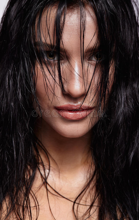 Portrait of a young brunette woman with shining wet make-up and. Shiny moist long hair hairdo royalty free stock photo