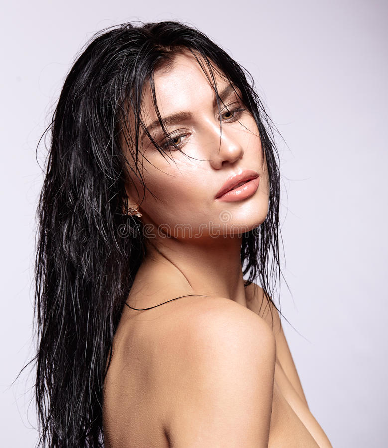 Portrait of a young brunette woman with shining wet make-up and. Shiny moist long hair hairdo stock images