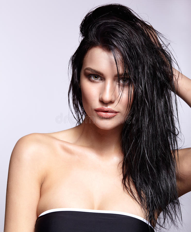 Portrait of a young brunette woman with shining wet make-up and. Shiny moist long hair hairdo stock photo