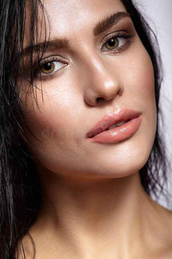 Portrait of a young brunette woman with shining wet make-up and. Shiny moist long hair hairdo royalty free stock photography