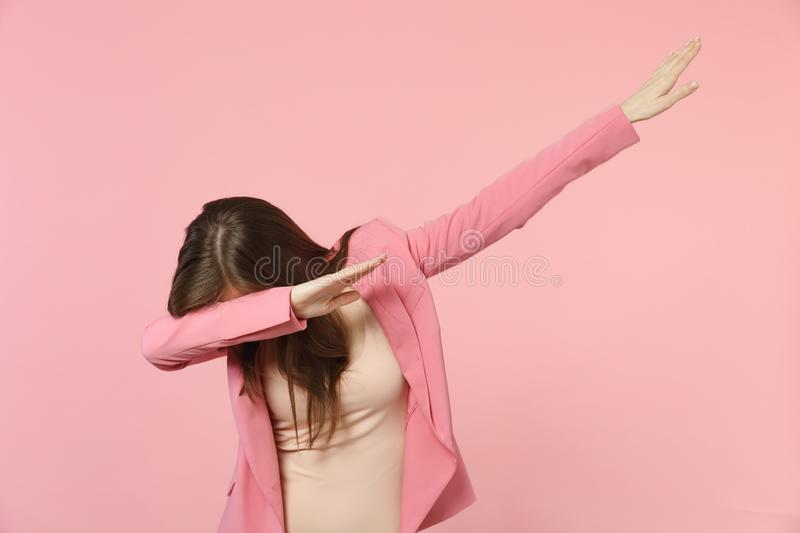 Portrait of young brunette woman wearing jacket standing and doing dab dance gesture isolated on pastel pink wall. Background in studio. People sincere emotions stock image