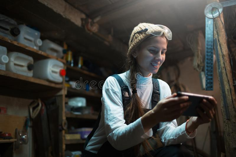Portrait of young builder girl standing in workshop use smartphone, wearing construction glasses. stock photography