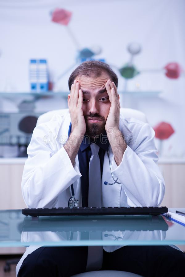 Portrait of young burnout doctor in his hospital cabinet. Young doctor overload of work at the hospital cabinet royalty free stock images