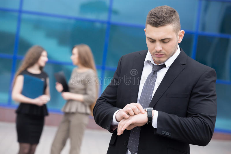Portrait of young business man looking at watch stock photo