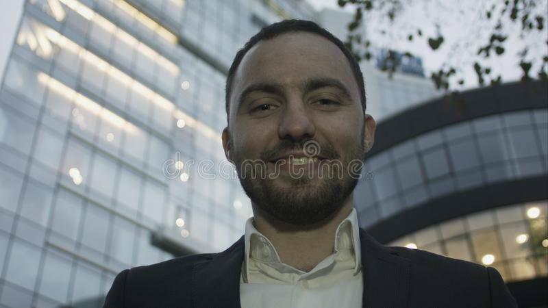 Portrait of young business man on office building background. Caucasian man with beard smiling. stock images