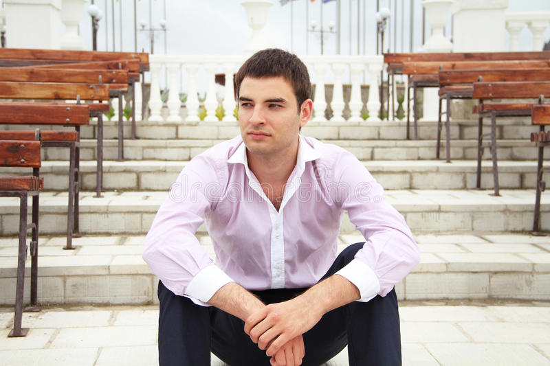 Portrait of young business man sitting on steps stock image