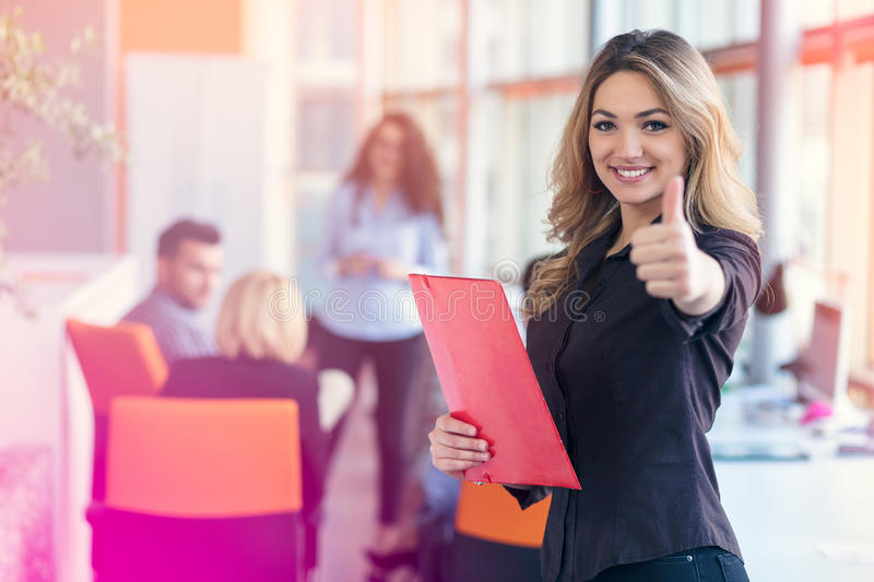 Portrait of young business woman at modern startup office interior showing thumbs up royalty free stock image