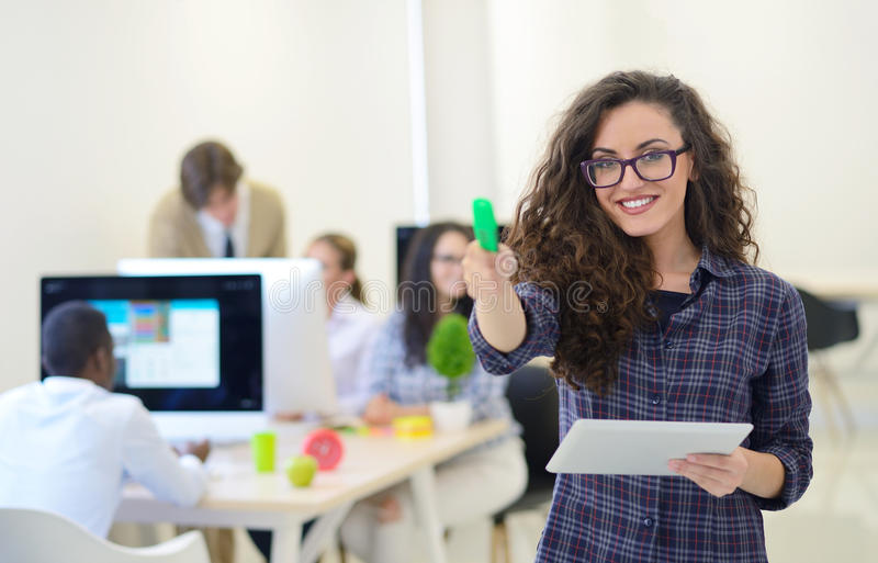Portrait of young business woman at modern startup office interior, team in meeting in background royalty free stock image