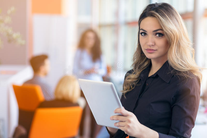 Portrait of young business woman at modern startup office interior, team in meeting in background. Portrait of young business women at modern startup office royalty free stock image
