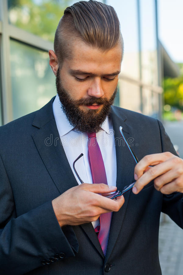 Portrait of a young businessman cleaning his eyeglasses outside royalty free stock image