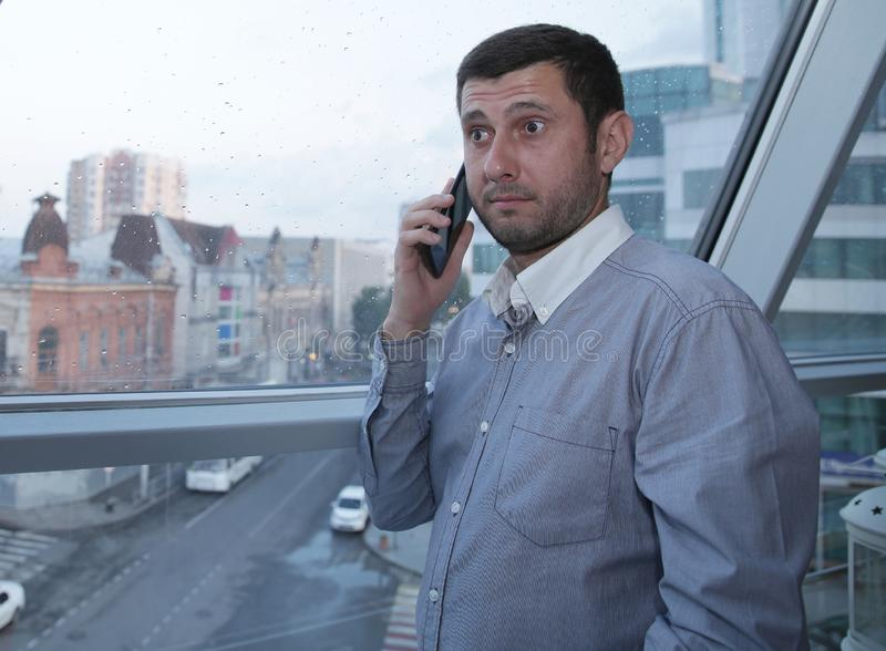 Young businessman emotionally talking on a mobile phone with astonishment on his face against the background of a panoramic window stock photo