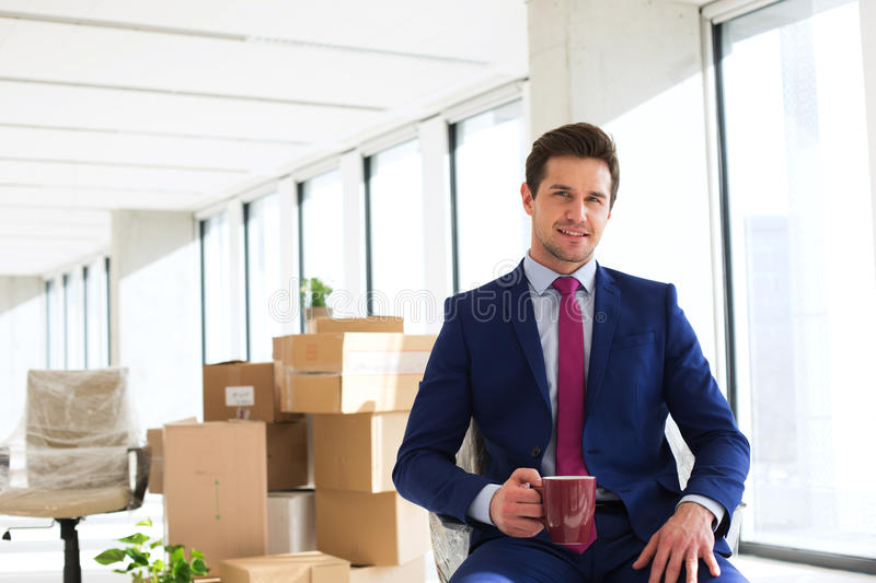 Portrait of young businessman having coffee with moving boxes in background at office stock photography