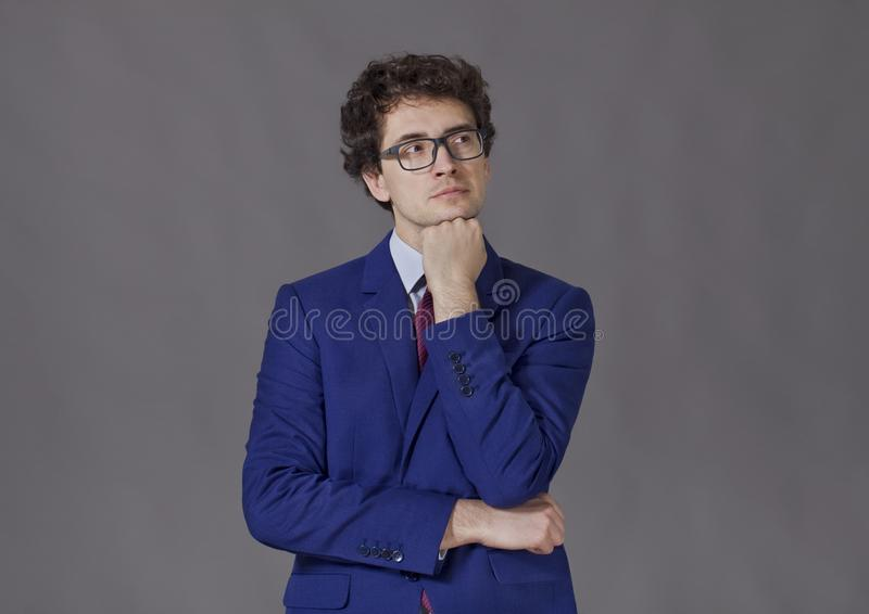 Portrait of young businessman keeping fist to his beard royalty free stock images