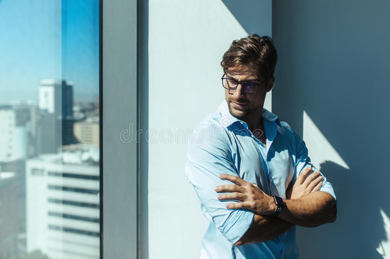 Portrait of a young businessman. Young man standing beside the window of a high rise building with sunshine in the background. Man wearing eyeglasses and arms stock photos