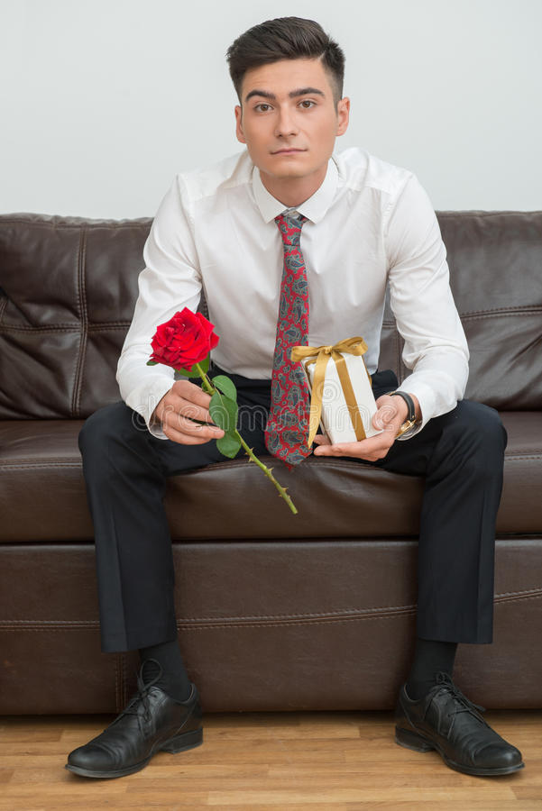 Portrait of young businessman in office. Full length Portrait of young serious businessman with a tie in office sitting on sofa and holding a flower and a stock image