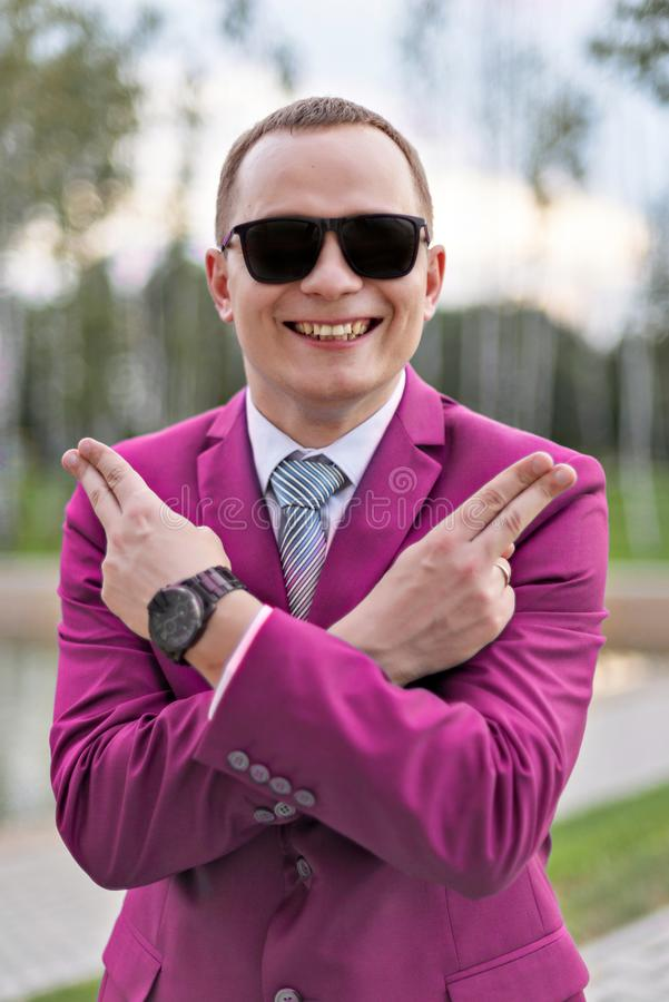 Portrait of a young businessman in pink suit joking shows pistols with fingers stock photos