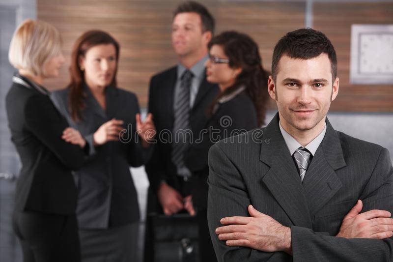 Portrait of young businessman. Wearing grey suit, standing with arms crossed in office royalty free stock photos