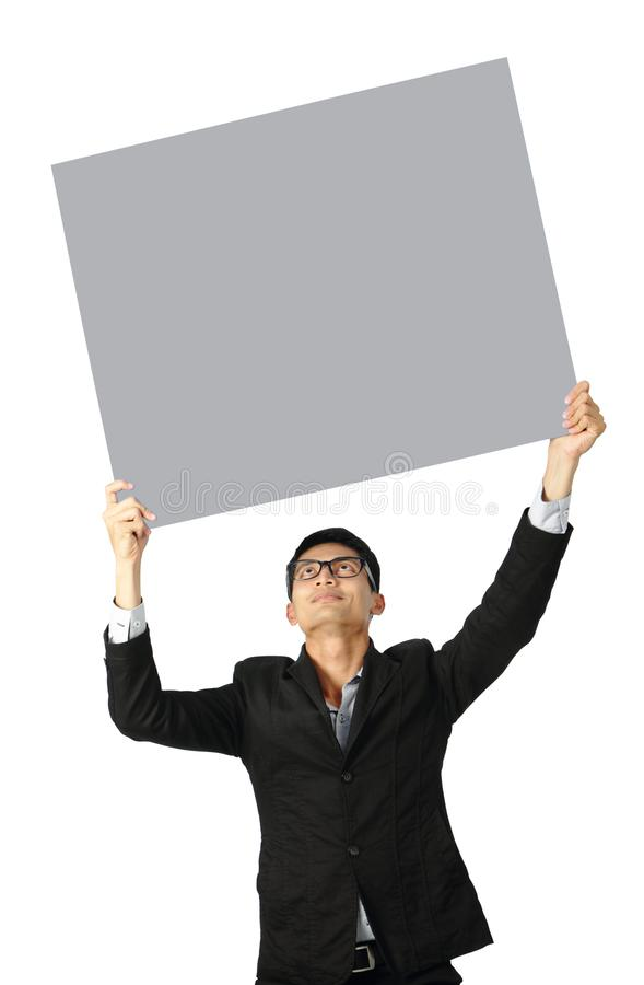 Portrait of  young businessman showing blank signboard clipping path royalty free stock image