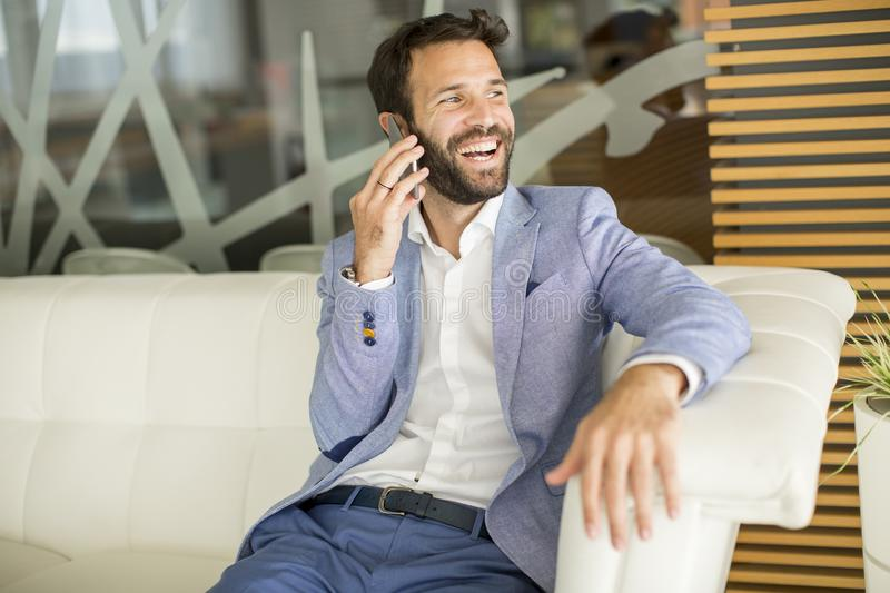 Happy young businessman sitting in office and using mobile phone royalty free stock photos