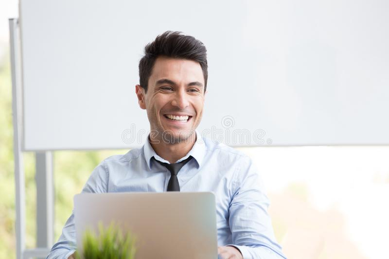 Portrait of young businessman smiling and working with laptop at office, stock image