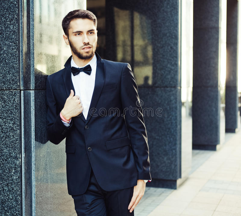 Portrait. Young businessman in a suit and bow tie posing on background of office building. market. course. success stock image