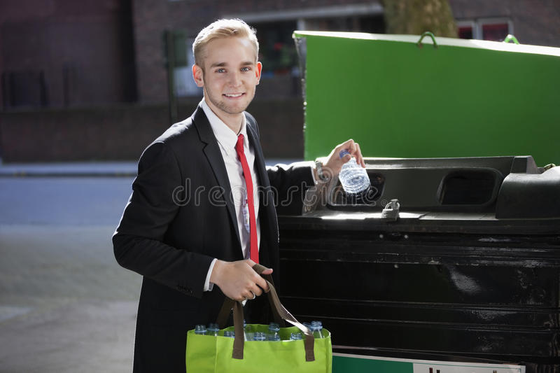 Portrait of young businessman throwing plastic bottles in bin royalty free stock photo