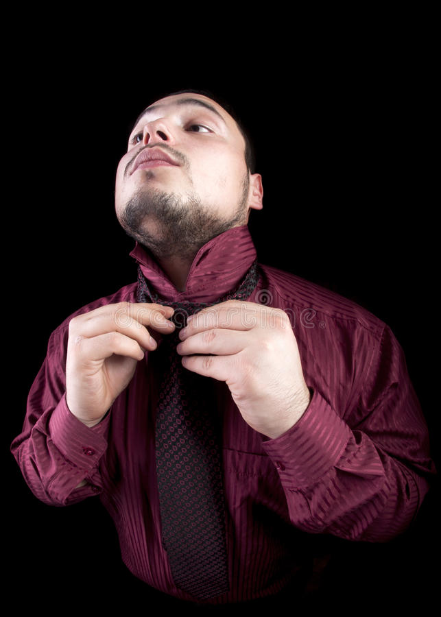 Portrait of young businessman who fixing his tie stock photo