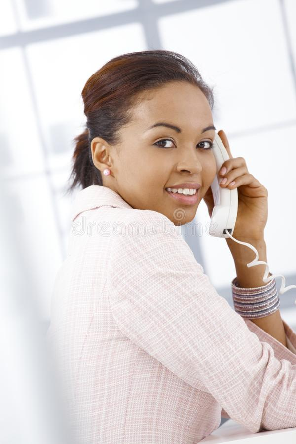 Portrait of young businesswoman on call. Portrait of young happy businesswoman on landline phone call in office stock images