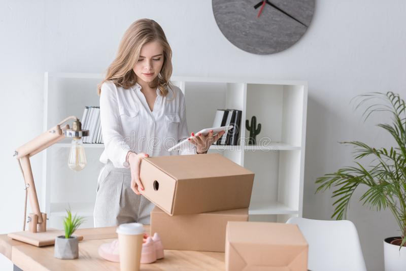 portrait of young businesswoman with cardboard box and tablet royalty free stock image