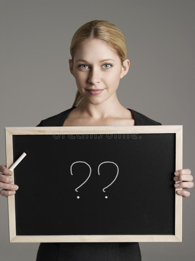 Portrait of young businesswoman holding blackboard with question marks royalty free stock images