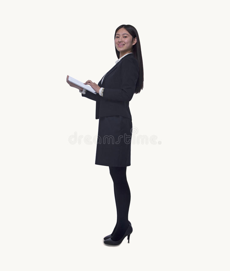 Portrait of young businesswoman holding a digital tablet, looking at camera, full length, studio shot royalty free stock image