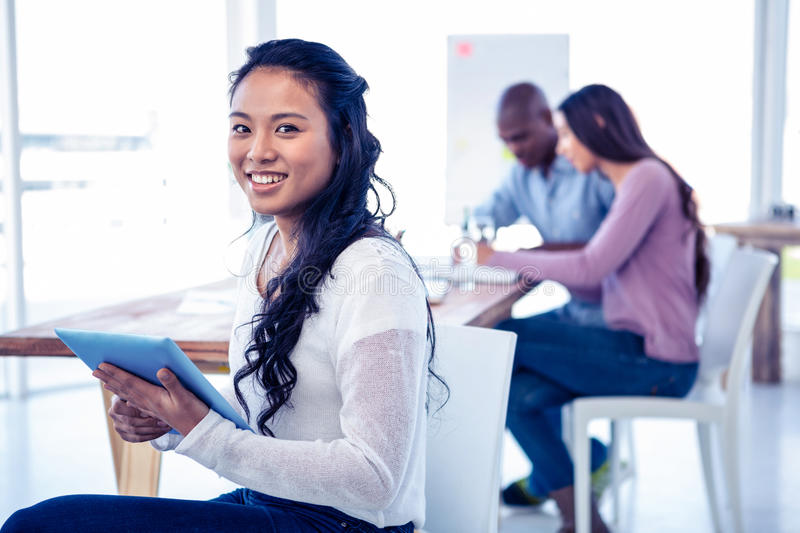 Portrait of young businesswoman holding tablet PC with colleagues in background. At creative office stock photo