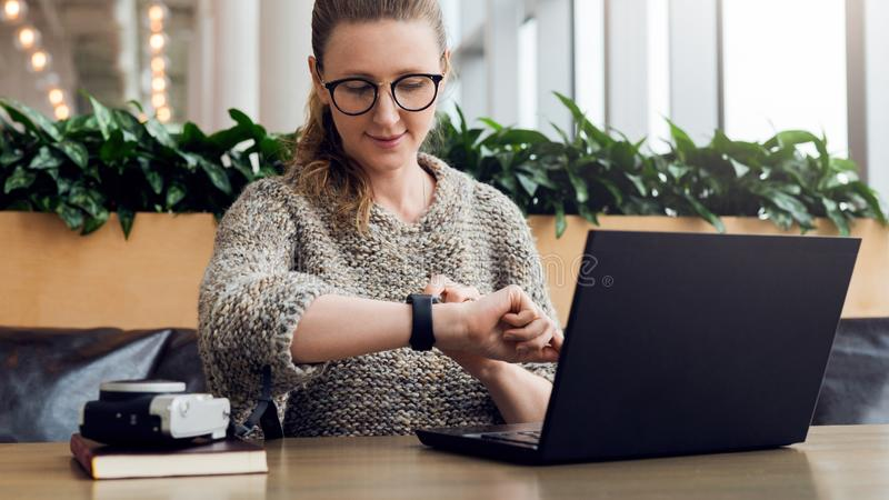 Portrait of young businesswoman sitting in cafe,working on laptop,looks at wrist watch. Online marketing, education. Portrait of young business woman in trendy royalty free stock photos