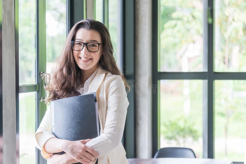 Portrait of young businesswoman smileing and holding document, . Success in business, job and education concept. Portrait of young businesswoman smileing and stock photography