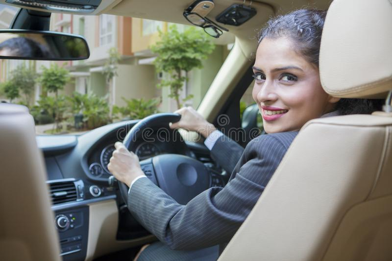 Smiling young businesswoman driving a car royalty free stock images
