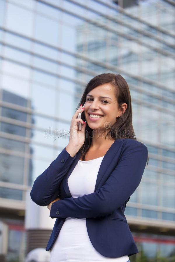 Young businesswoman talking over the mobile phone in fron of off. Portrait of young businesswoman talking over the mobile phone in fron of office building stock photo
