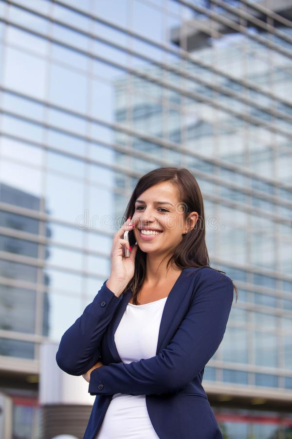 Young businesswoman talking over the mobile phone in fron of off. Portrait of young businesswoman talking over the mobile phone in fron of office building stock photography