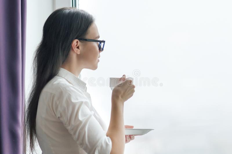 Portrait of young businesswoman in white shirt glasses with cup of coffee, woman looking out the window, office in skyscraper,. Cloudy day stock images