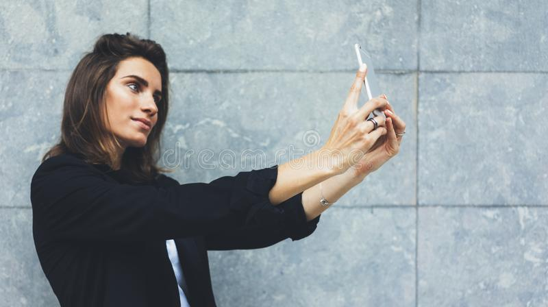 Portrait young businesswomen in black suit using smartphone on background concrete gray wall mockup, pretty hipster royalty free stock photography