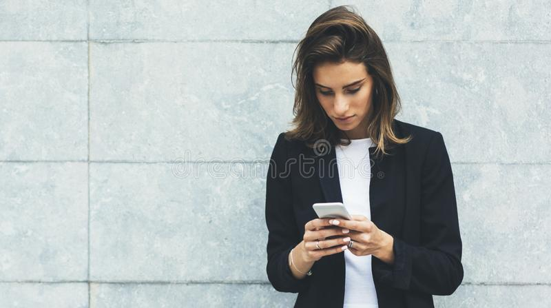 Portrait young businesswomen in black suit using smartphone isolated on background concrete gray wall mockup, hipster manager stock image