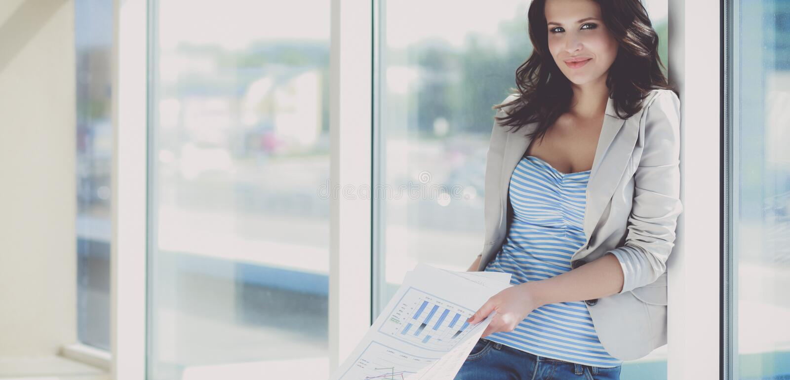 Portrait of young busineswoman standing in office lobby.  stock photos