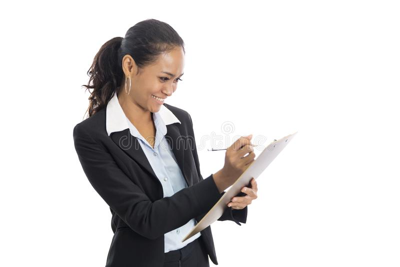Young busineswoman writing report while standing. Portrait of young busineswoman writing report while standing isolated on white background stock image