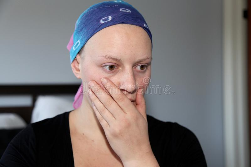 Portrait of a young cancer patient in a headscarf holding hand to mouth royalty free stock photos