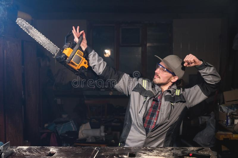 Portrait of a young carpenter in a workshop with a chainsaw in the hands of a pose representing a bodybuilder. Jokes and. Fun at the workplace carpenter stock images